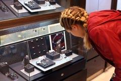 Молодая женщина рассматривает ювелирные изделия в магазине ювелирных изделий. Стоковые Изображения RF