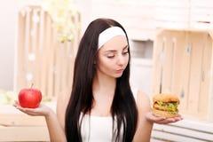 Молодая женщина решает между гамбургером и яблоком Здоровое Lifes стоковая фотография rf