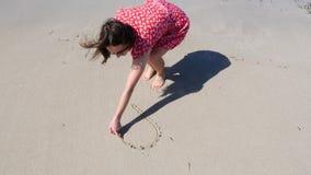 Молодая женщина рисуя сердце на песке нося красное платье Чертежи пляжа моря сердца акции видеоматериалы
