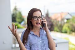 Молодая женщина риэлтора вызывая и обсуждает outdoors Стоковое фото RF