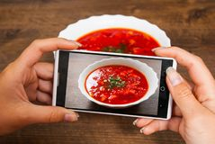 Молодая женщина рук принимая фото еды на smartphone Стоковые Фотографии RF