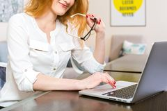 Молодая женщина рук с длинными красными волосами в белой рубашке и стеклами для зрения работает, печати, пользы серая компьтер-кн Стоковое Изображение