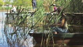 Молодая женщина рыболов удит на озере леса, держа рыболовную удочку переплетает катушку акции видеоматериалы