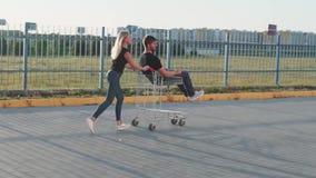 Молодая женщина свертывает привлекательного парня в вагонетке на парковке супермаркета на заходе солнца ( видеоматериал