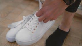 Молодая женщина связывает вверх ее шнурки на белых тапках в магазине Конец-вверх сток-видео