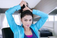 Молодая женщина связывая ее длинные волосы в спальне стоковые фотографии rf