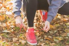 Молодая женщина связывая шнурки идущих ботинок перед внешний jogging стоковое фото