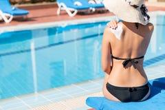 Молодая женщина сидит бассейном и прикладывает сливк солнца на ее плече бассейном Фактор предохранения от Солнца в каникулах, кон стоковые изображения rf