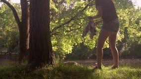 Молодая женщина сидит вниз на траве около дерева в парке видеоматериал