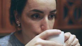 Молодая женщина сидит в кафе, влюбленностях для того чтобы запахнуть и глоточке чашка кофе сток-видео