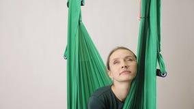 Молодая женщина сидит на гамаке вымотанном и упаденном на гамак Воздушная aero разминка тренера фитнеса мухы meditates акции видеоматериалы