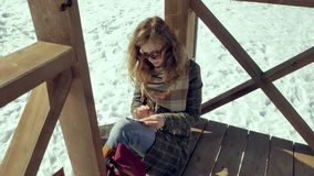Молодая женщина сидит на деревянной веранде, молчком касаясь самолету бумаги origami с ее пальцами и кладя ее на ее видеоматериал