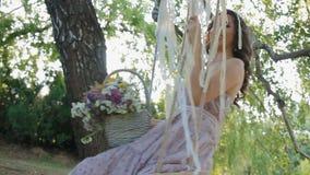 Молодая женщина сидит на качании и колеблется акции видеоматериалы