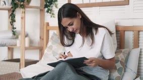 Молодая женщина сидит на кровати и пишет страницы утра в дневнике, замедленном движении сток-видео