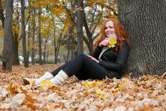 Молодая женщина сидит около дерева в парке осени и прочитала книгу, листья желтого цвета Стоковая Фотография RF