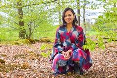 Молодая женщина сидя весной лес Стоковое Изображение RF