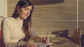 Молодая женщина сидя в кафе с наушниками и делая примечания в тетради сток-видео