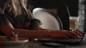Молодая женщина сидя в кофейне на деревянном столе, выпивая кофе и используя smartphone На таблице компьтер-книжка девушка акции видеоматериалы
