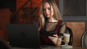 Молодая женщина сидя в кофейне на деревянном столе, выпивая кофе и используя smartphone На таблице компьтер-книжка девушка видеоматериал