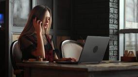 Молодая женщина сидя в кофейне на деревянном столе, выпивая кофе и используя smartphone На таблице компьтер-книжка девушка сток-видео
