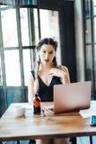 Молодая женщина сидя в кофейне стоковое изображение rf