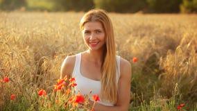 Молодая женщина сидя в пшеничном поле, освещенном солнцем после полудня, немногие re стоковое изображение