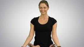 Молодая женщина сидя в раздумье представления йоги лотоса практикуя на белой предпосылке Стоковое фото RF