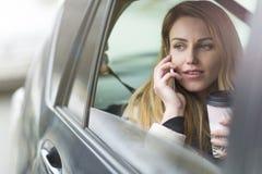 Молодая женщина сидя в такси Стоковые Изображения