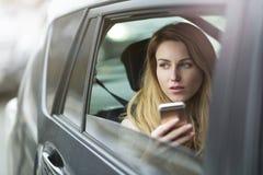 Молодая женщина сидя в такси Стоковое фото RF