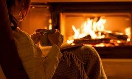 Молодая женщина сидя дома и читая книгу Стоковое фото RF