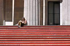 Молодая женщина сидя и книга чтения на красных лестницах перед федеральным Hall во фронте фронт, Уолл-Стрит, Манхэттен, Нью-Йорк  стоковое изображение