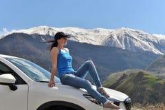 Молодая женщина сидя на клобуке автомобиля и наслаждаясь окружающим ландшафтом стоковые фотографии rf