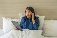 Молодая женщина сидя на кровати и используя телефон и планшет стоковая фотография rf