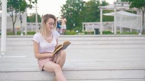 Молодая женщина сидя на лестницах читая книгу в городском парке акции видеоматериалы