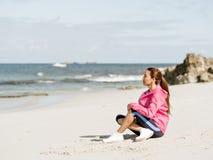 Молодая женщина сидя на пляже в sportswear Стоковое Фото