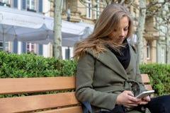 Молодая женщина сидя на скамейке в парке с smartphone Стоковая Фотография RF