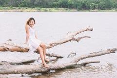 Молодая женщина сидя на стволе дерева на озере и усмехаться Стоковое фото RF