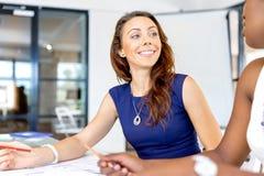 Молодая женщина сидя на столе в офисе и работая на светокопии Стоковая Фотография RF