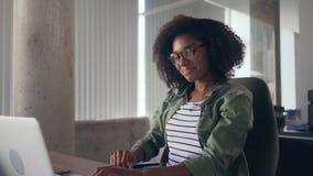 Молодая женщина сидя на столе перед ноутбуком протягивая ее оружия сток-видео