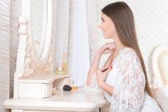 Молодая женщина сидя на таблице шлихты Стоковое Изображение