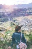 Молодая женщина сидя на утесе с рюкзаком и смотря к горизонту Остров Бали Вулкан Batur стоковые фотографии rf