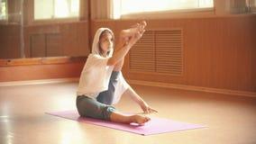Молодая женщина сидя на циновке йоги и делая ногу протягивая тренировки - студию танца видеоматериал