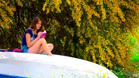 Молодая женщина сидя на шлюпке видеоматериал