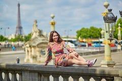 Молодая женщина сидя около Эйфелевой башни в Париже стоковые фото