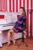 Молодая женщина сидя рядом с роялем Длинние прямые волосы Conce стоковые фото