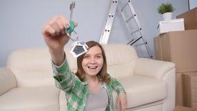Молодая женщина сидя с коробками и держа ключи к квартире