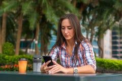 Молодая женщина сидя outdoors читая и печатая сообщения на ее smartphone Стоковые Фотографии RF