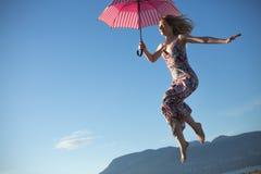 Молодая женщина скача держащ розовый зонтик стоковые фотографии rf