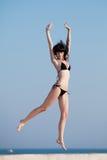 Молодая женщина скача на открытый воздух Стоковая Фотография