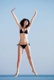 Молодая женщина скача на открытый воздух Стоковые Фото